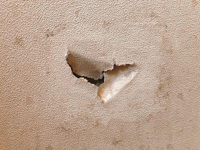 たたいて部屋の壁をへこませた跡